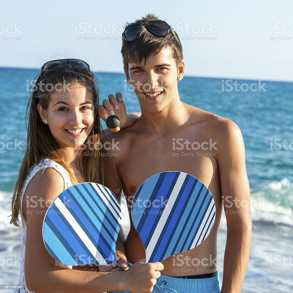 Teen couple avec raquettes de tennis sur la plage. photo libre de droits