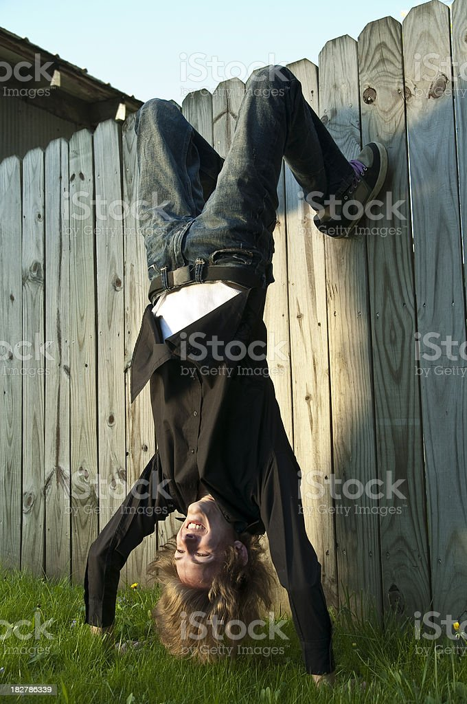 Teen doing a Handstand against wood fence stock photo