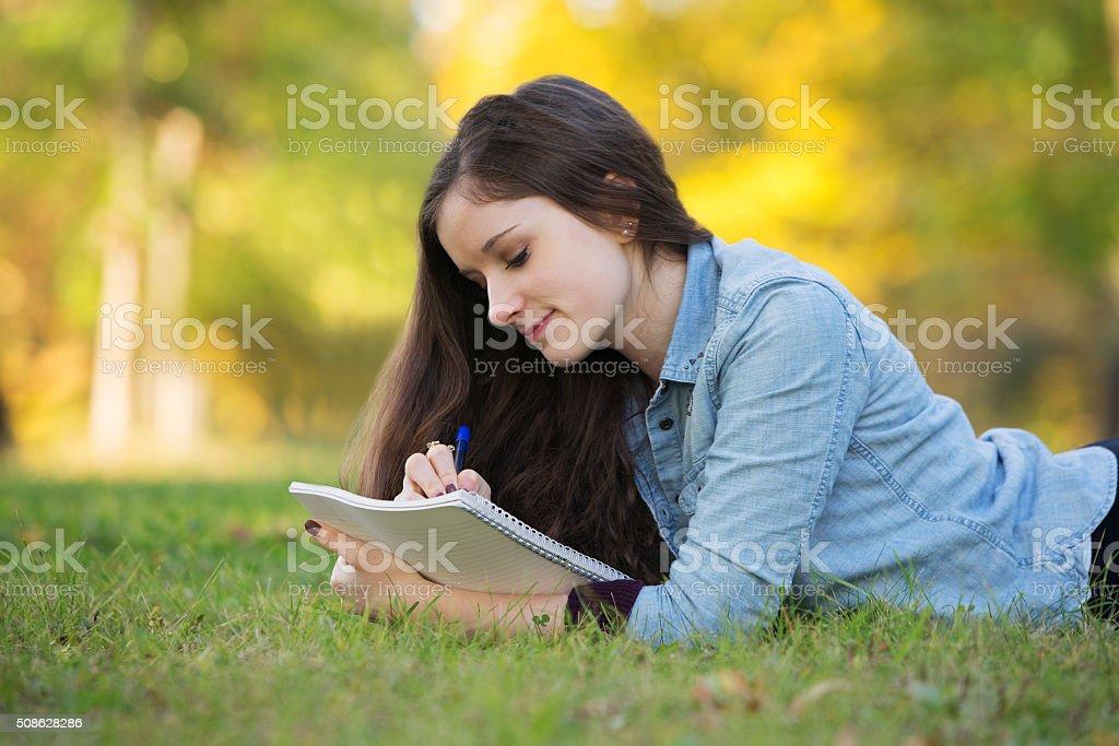 Teen Doing Homework Outside stock photo