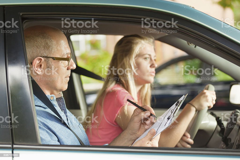 Teen Driver Evaluated by Examiner in Driver Examination_ stock photo
