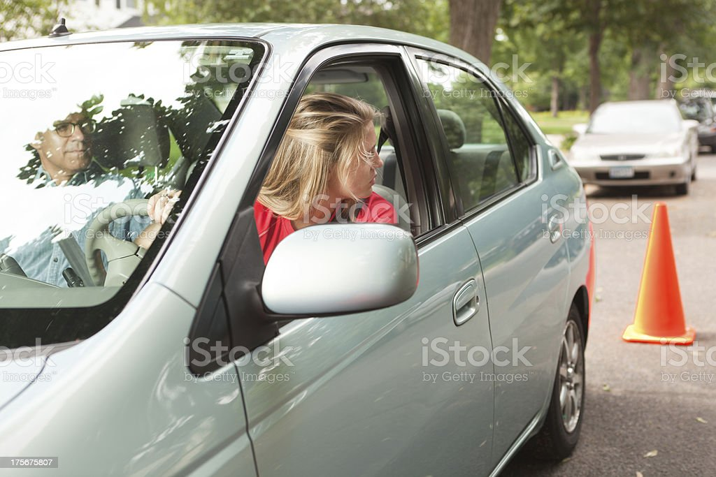 Teen Driver Learning Parallel Parking with Driving Instructor and Cone stock photo