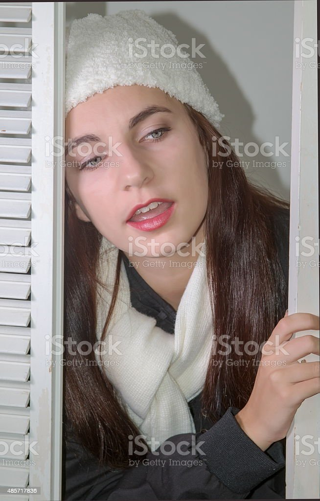 Teen Female Checking To See Who Is Under Her Window stock photo