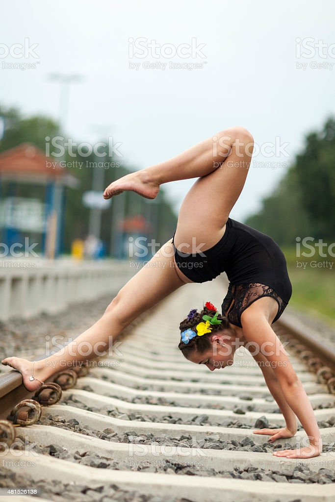 Teen Female Gymnast Doing Back Walkover On Railway Track stock photo