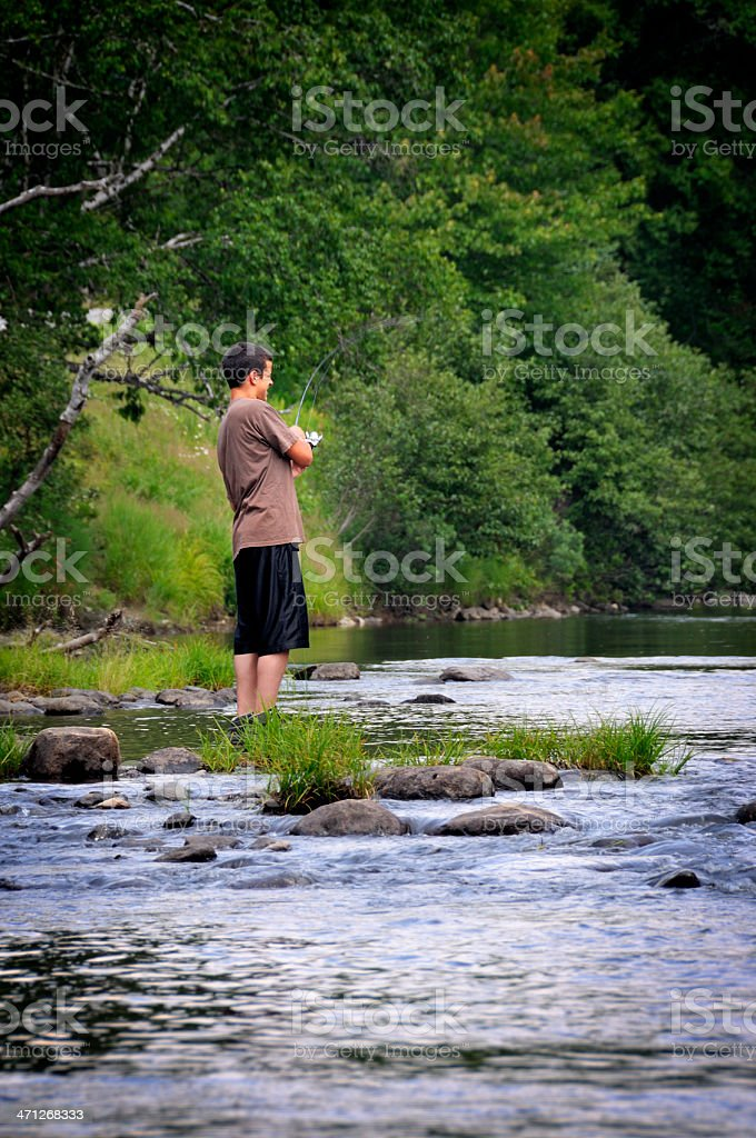 Teen Fighting Large Fish on the Androscoggin River stock photo