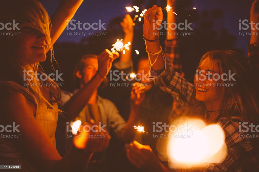 Teen friends dancing and celebrating with sparklers at night stock photo