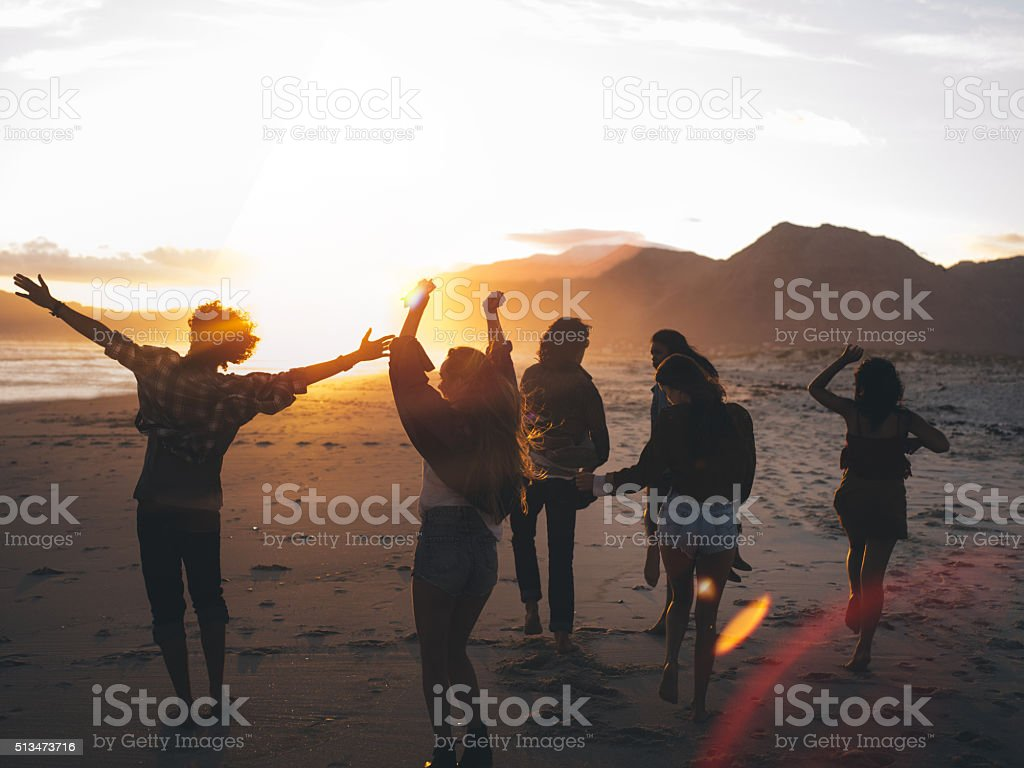 Teen friends dancing on the beach at sunset stock photo
