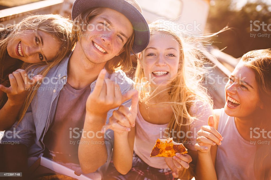 Teen friends eating pizza together outdoors with sun flare stock photo