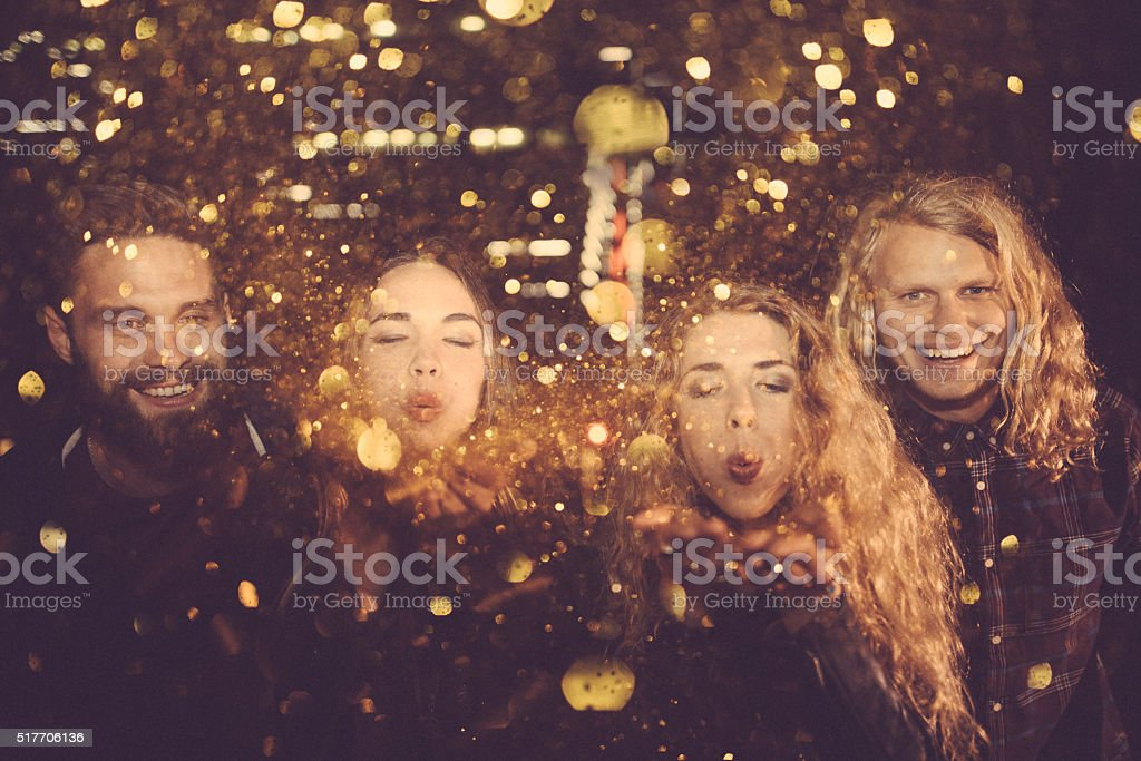 Teen friends enjoying night party with golden confetti stock photo