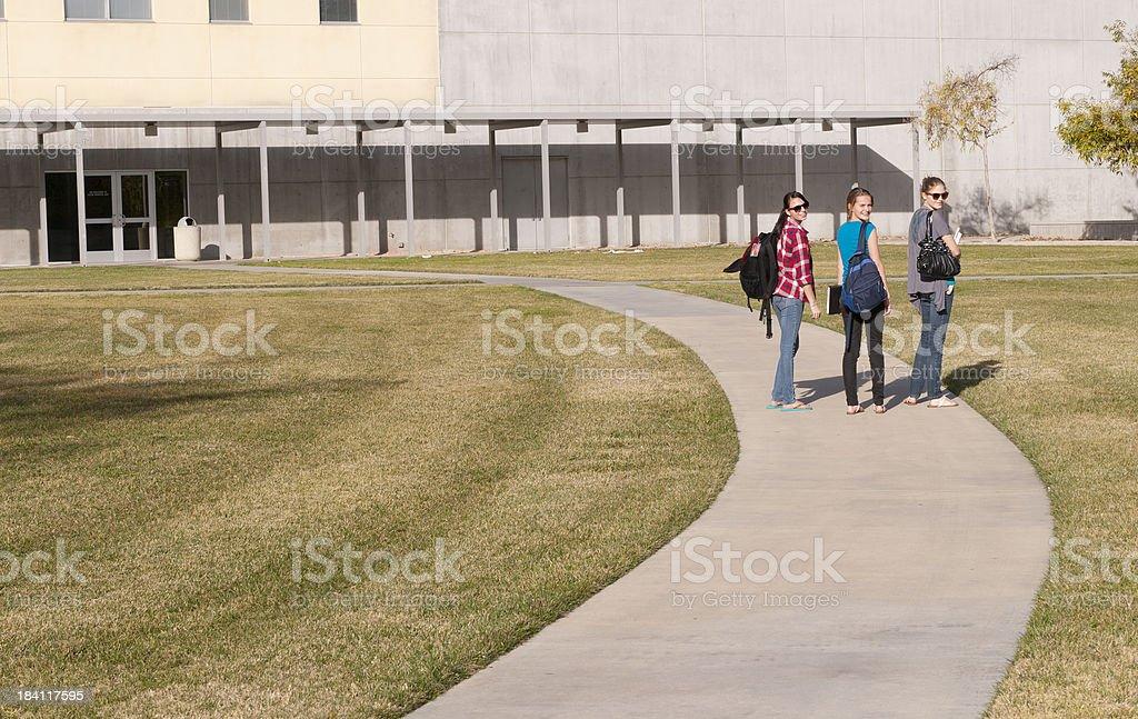 Teen friends looking back near school royalty-free stock photo