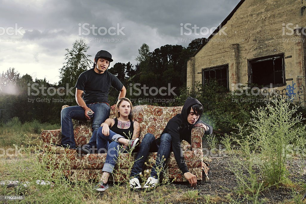 Teen Friends Sitting Outdoors on a Vintage Couch royalty-free stock photo