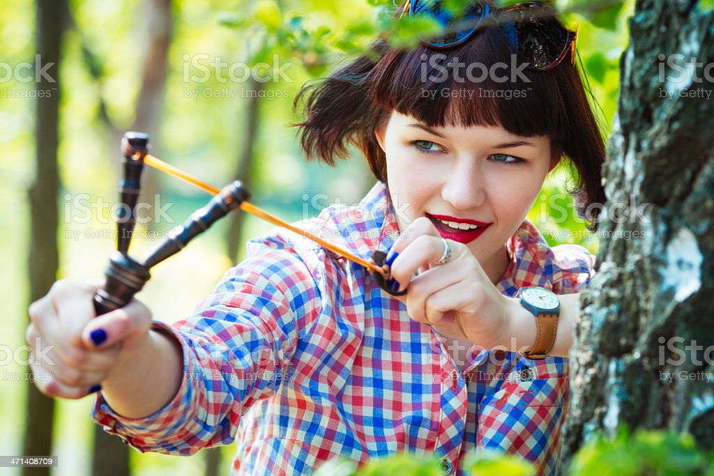Teen girl aiming a slingshot in the woods royalty-free stock photo