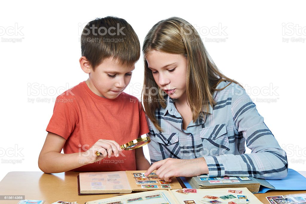 Teen girl and boy looking his stamp collection isolated stock photo