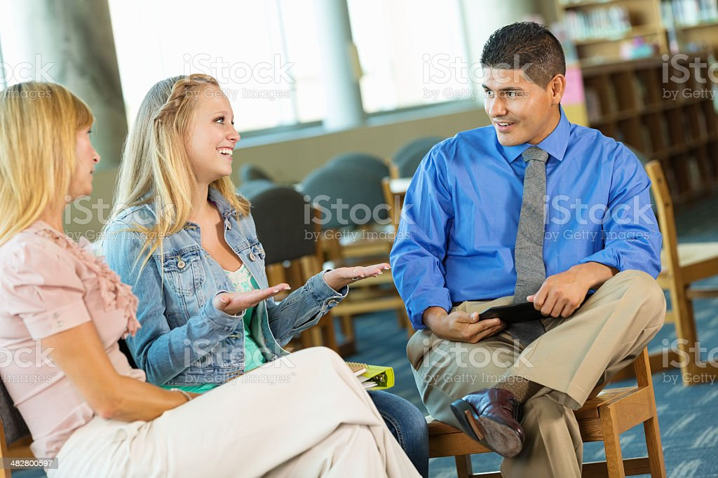 Teen girl and mother meeting with therapist or counselor stock photo