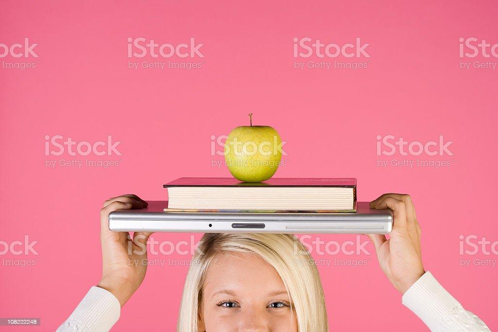 Teen girl balances school items on her head royalty-free stock photo