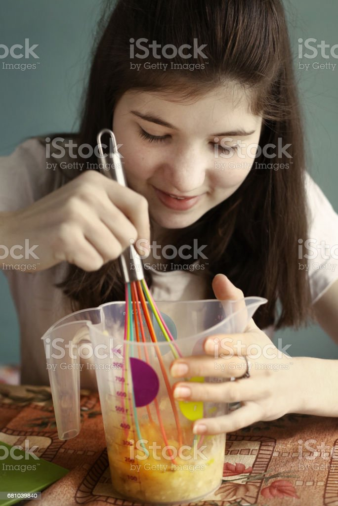 teen girl cooking banana cake stock photo