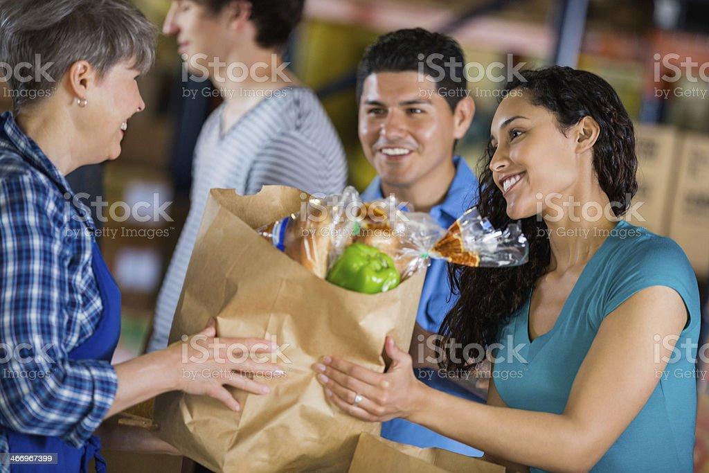 Teen girl donating bag at community food drive royalty-free stock photo