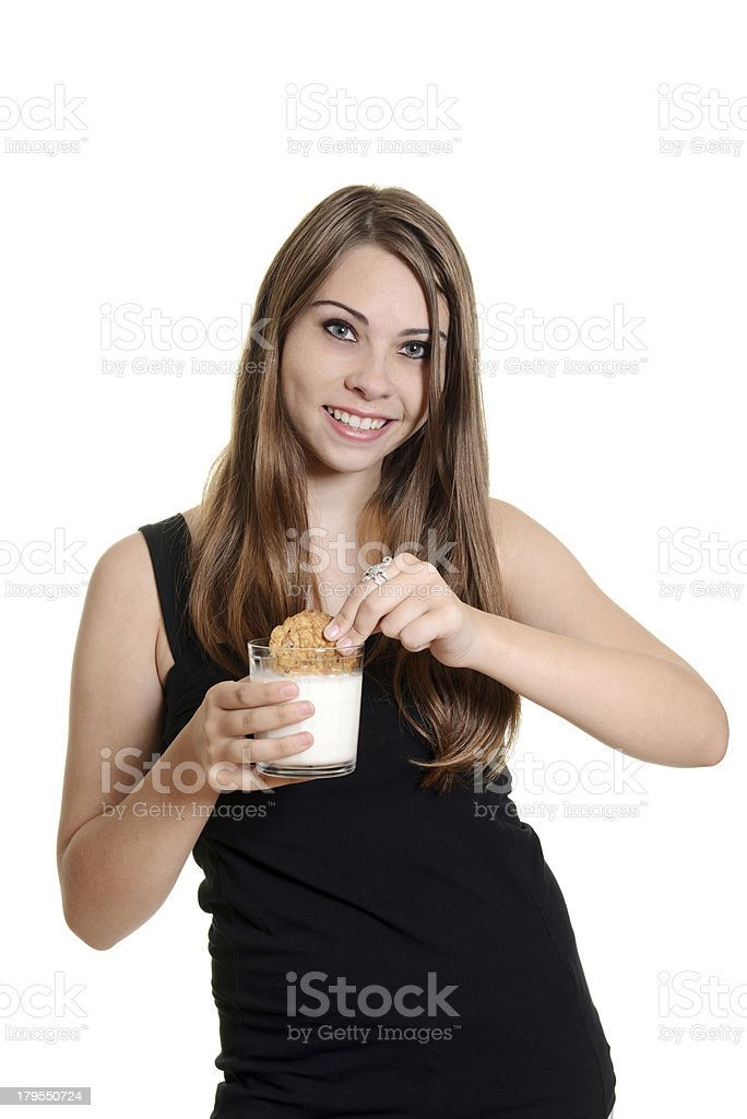teen girl dunking oatmeal cookie in milk royalty-free stock photo