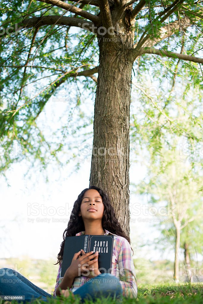 Teen girl holding Bible with eyes closed stock photo