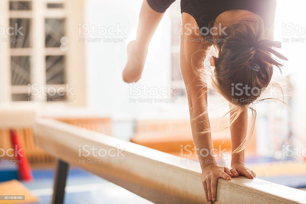 Girl gymnast trains in the gym