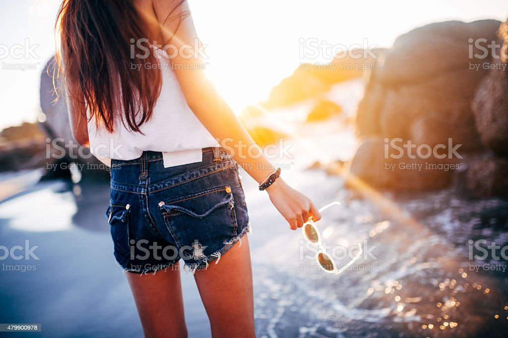 Teen girl in denim shorts at the beach with sunglasses stock photo