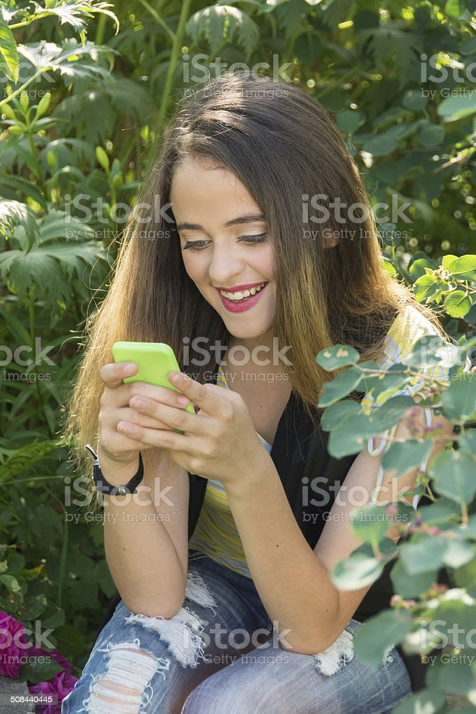 Teen girl in garden, laughing at text on phone.. stock photo