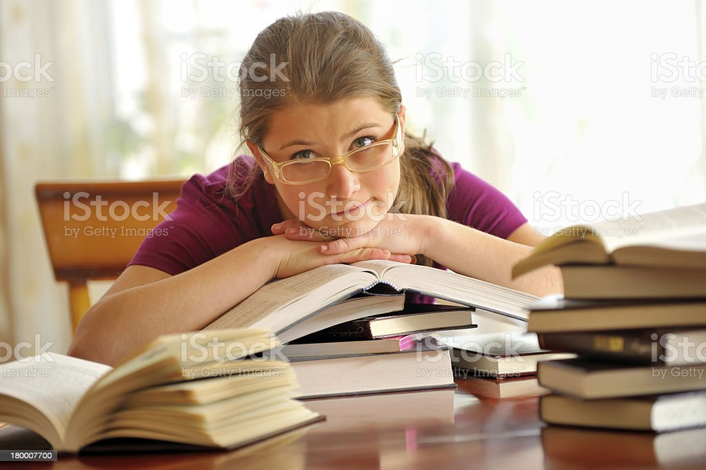 Teen girl learning at the desk, looking up royalty-free stock photo
