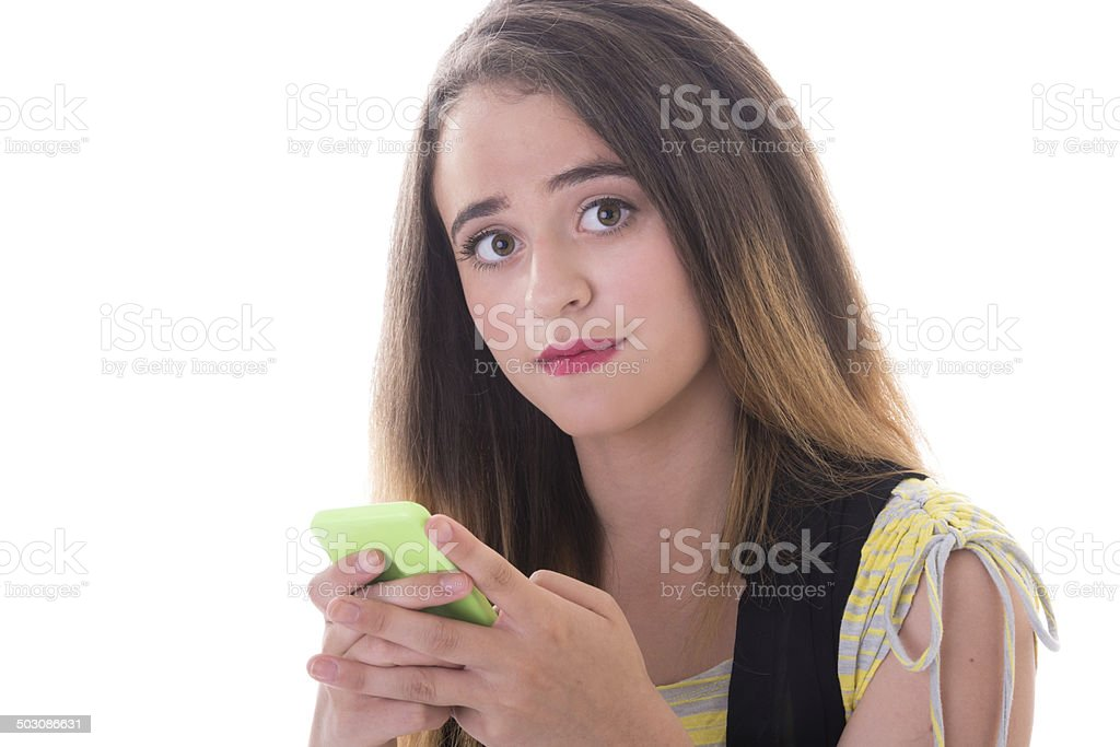 Teen girl looking up from smart phone. stock photo