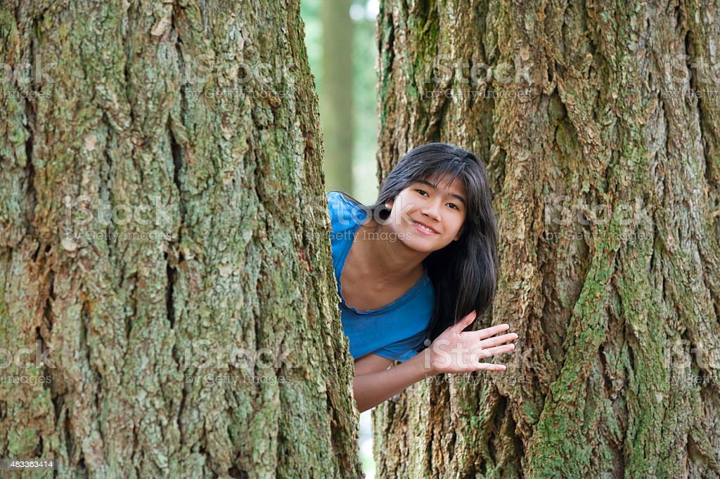 Teen girl peeking through trees, waving and smiling stock photo
