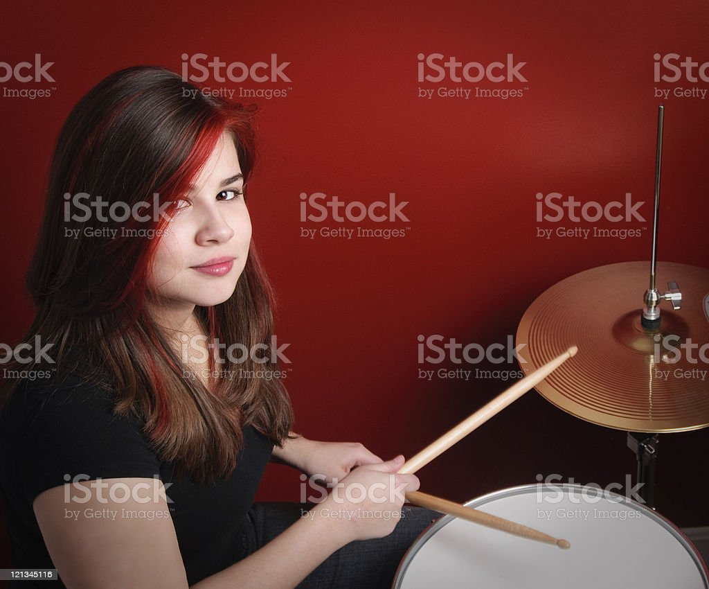 Teen girl playing drums stock photo