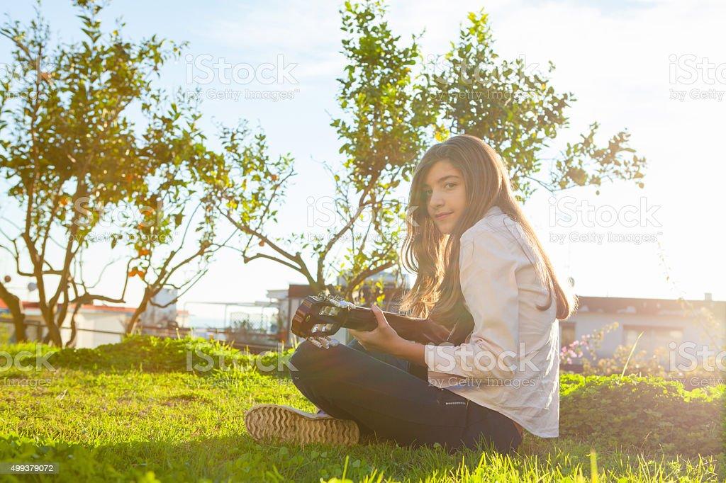 Teen Girl Playing Guitar on Grass stock photo