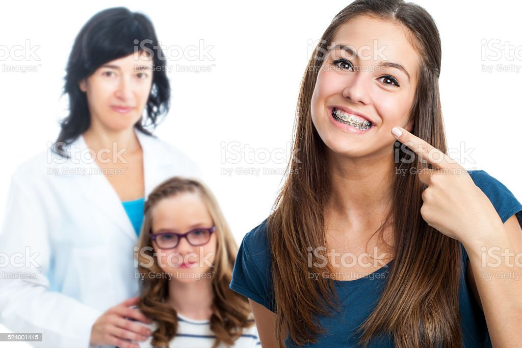 Teen girl pointing at dental barces with doctor in background. stock photo