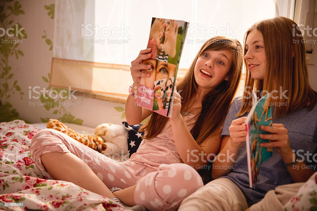 Teen girl showing her friend a new fashion magazine stock photo