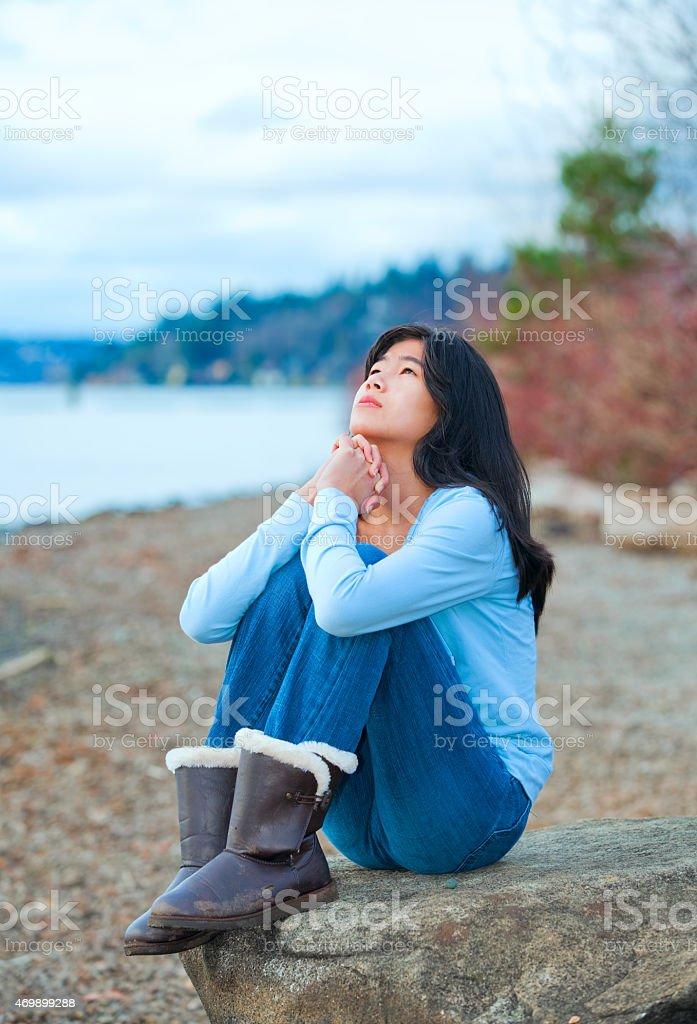 Teen girl sitting on boulder along lake shore praying stock photo