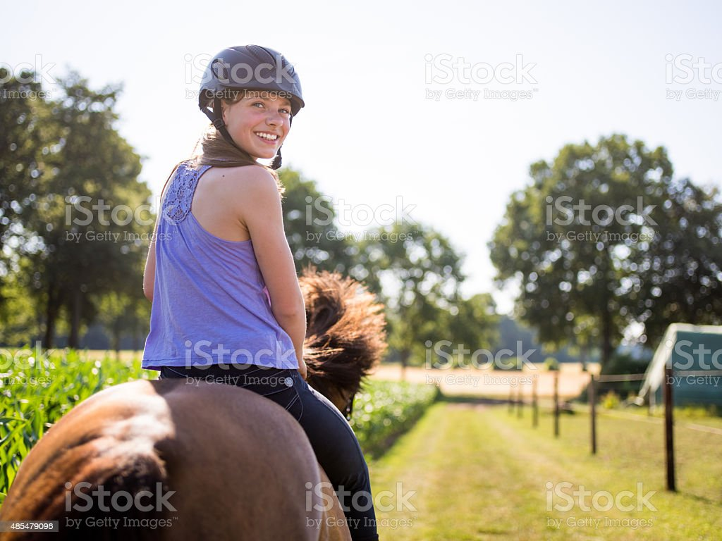 Teen girl smiling and looking back while riding her horse stock photo