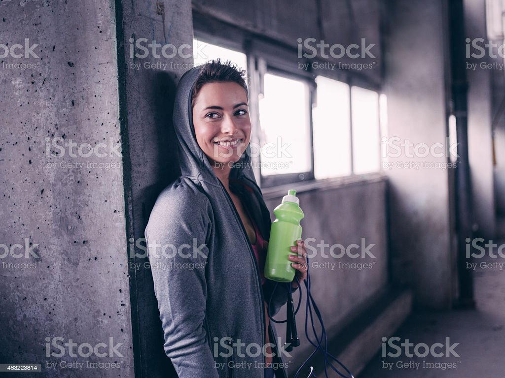 Teen girl smiling holding water bottle after a working out stock photo