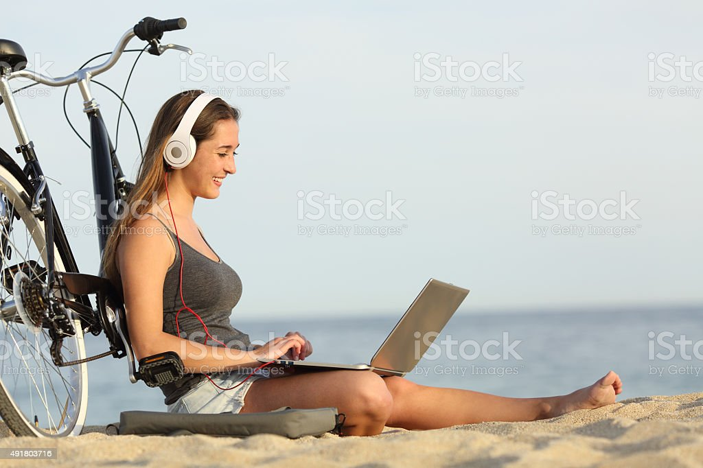 Teen girl studying with a laptop on the beach stock photo
