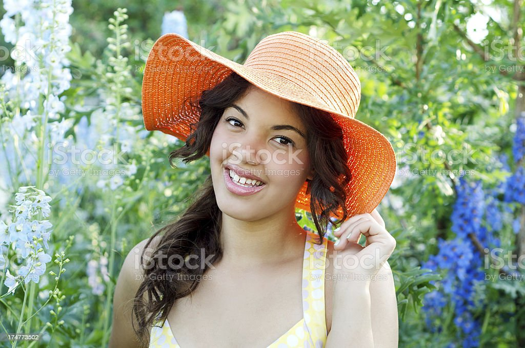 Teen girl touching orange hat in garden stock photo