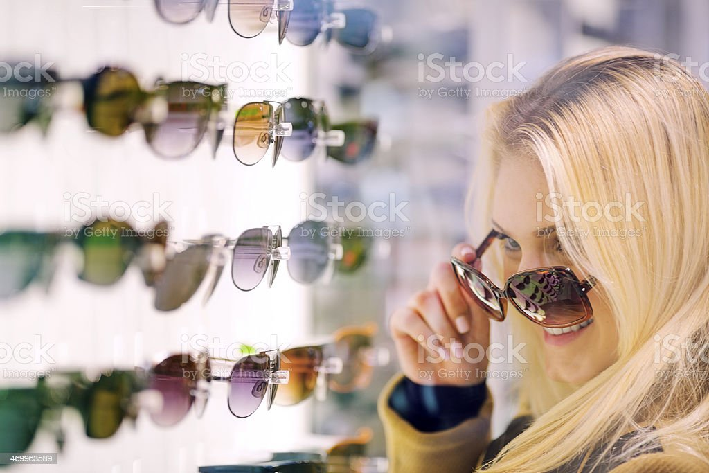 Teen girl trying  sunglasses in store stock photo
