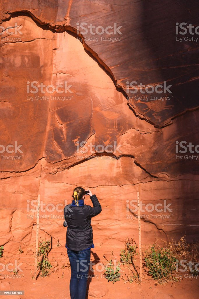 Teen girl uses smartphone to photograph ancient rock art in Monument Valley stock photo