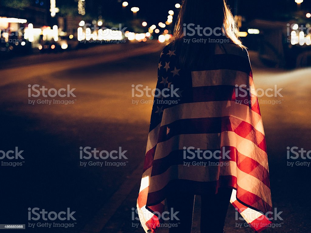 Teen girl walking alone on city street with American flag stock photo