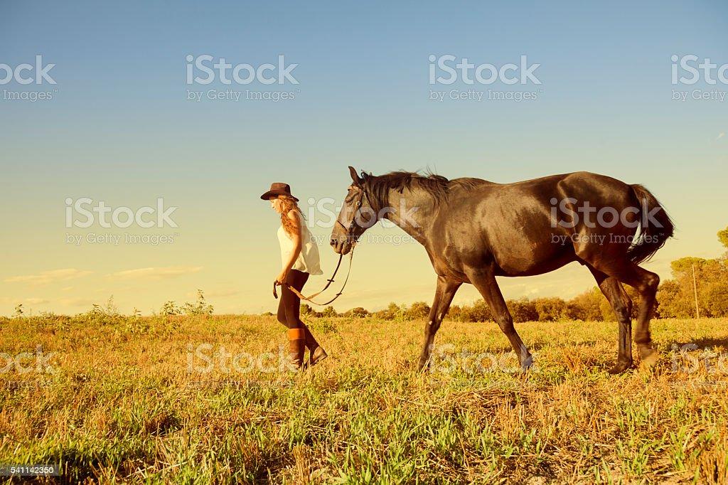 Teen girl walking her horse stock photo