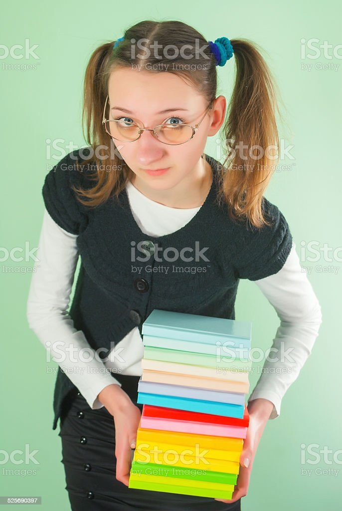 Teen girl with a stack of books stock photo