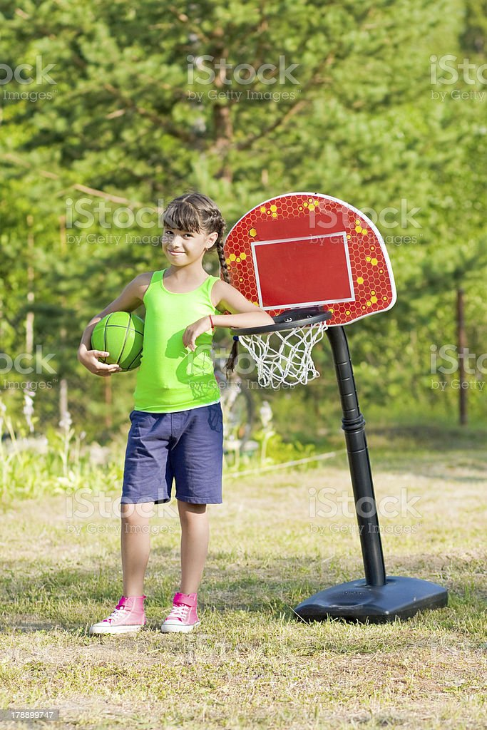 Teen girl with basketball in summer park royalty-free stock photo