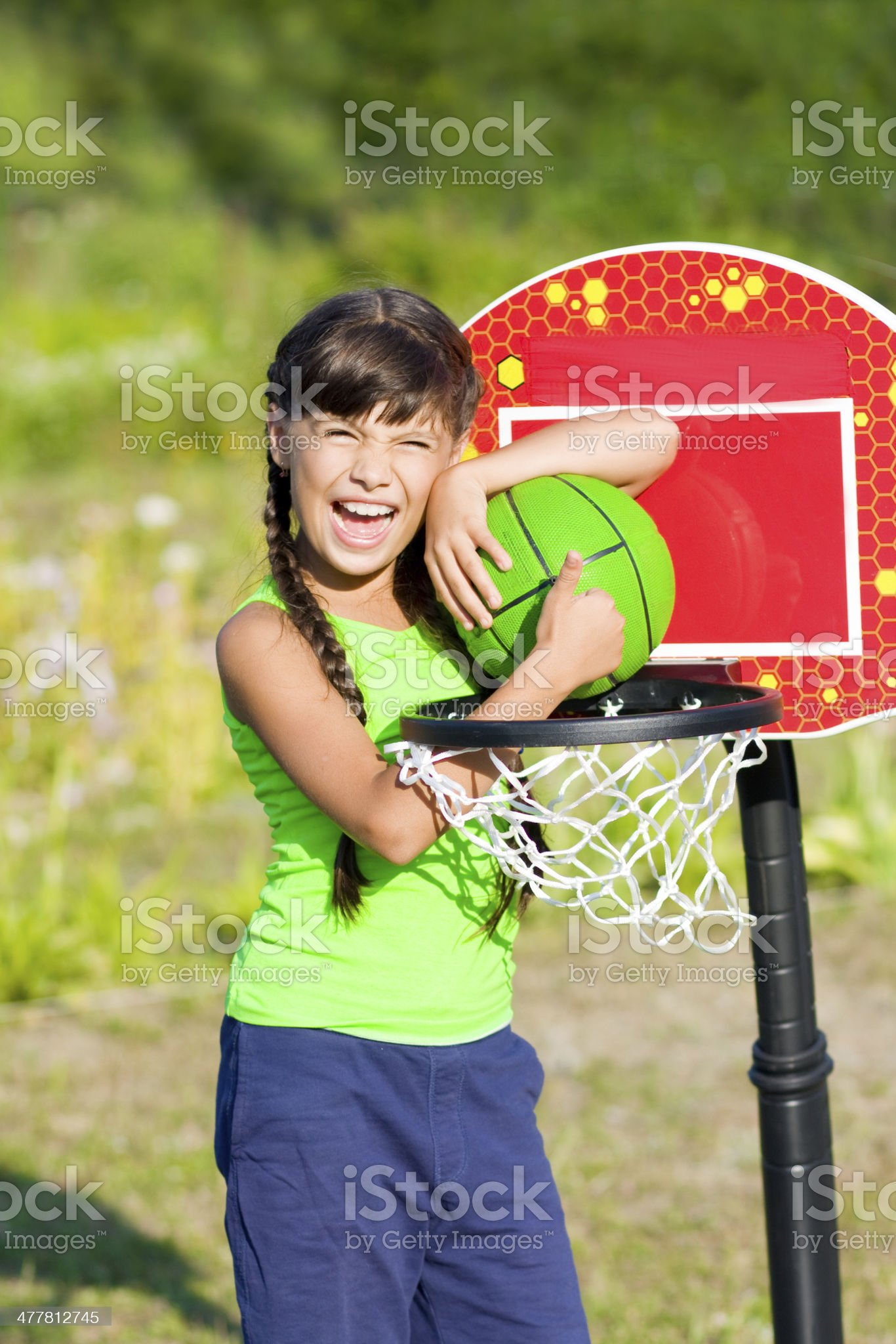Teen girl with basketball shows thumb up royalty-free stock photo