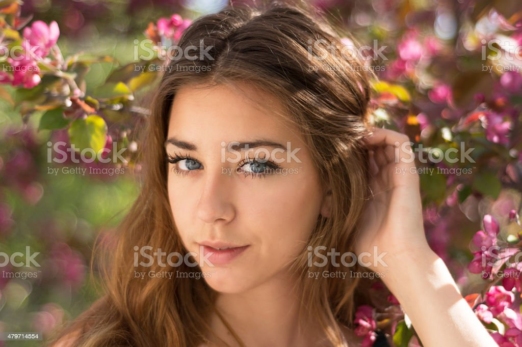 Teen girl, with blue eyes tucking hair behind ear, smiling. stock photo