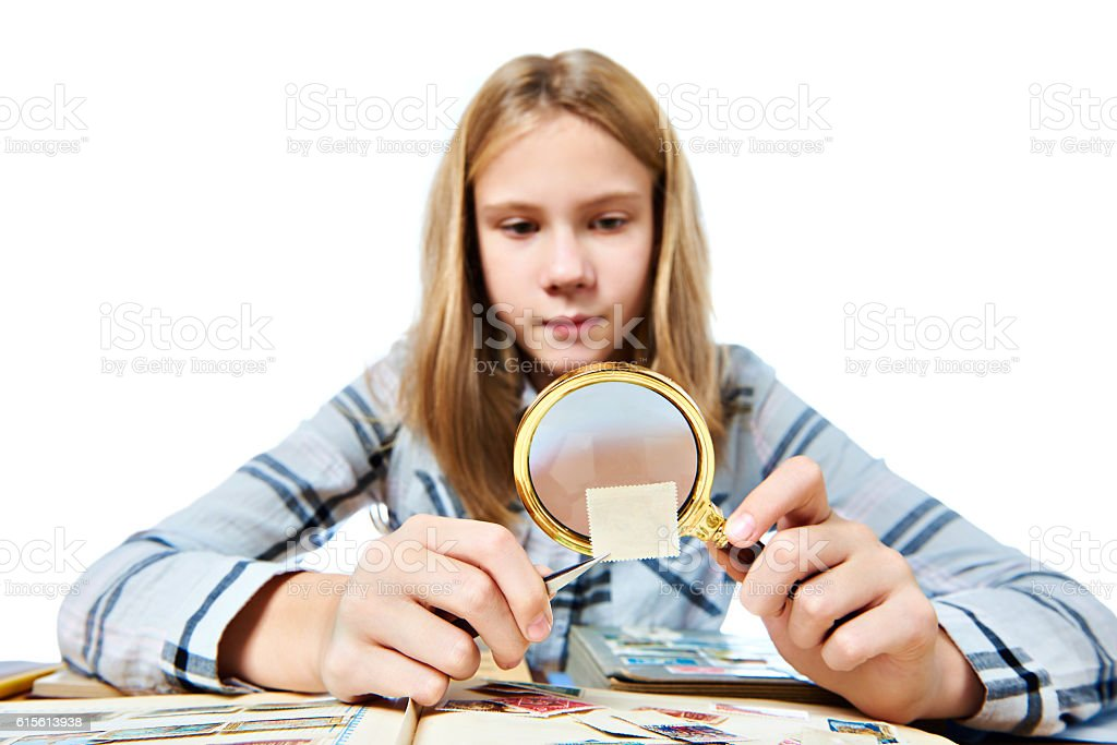 Teen girl with magnifier looks his stamp collection isolated stock photo