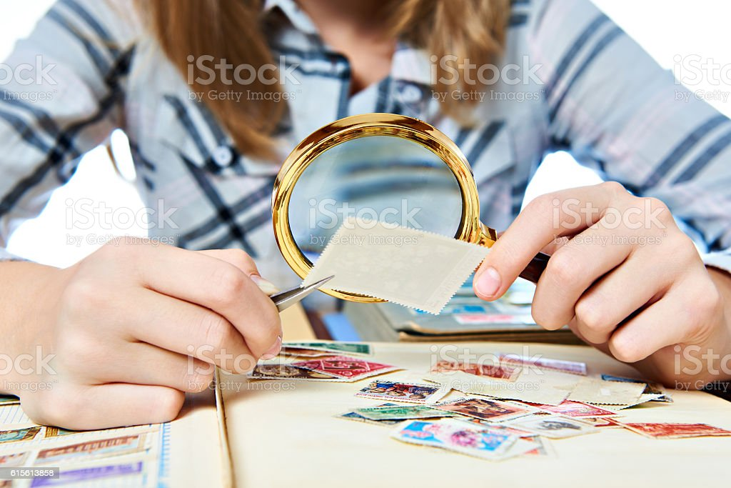 Teen girl with magnifier looks his stamp collection stock photo