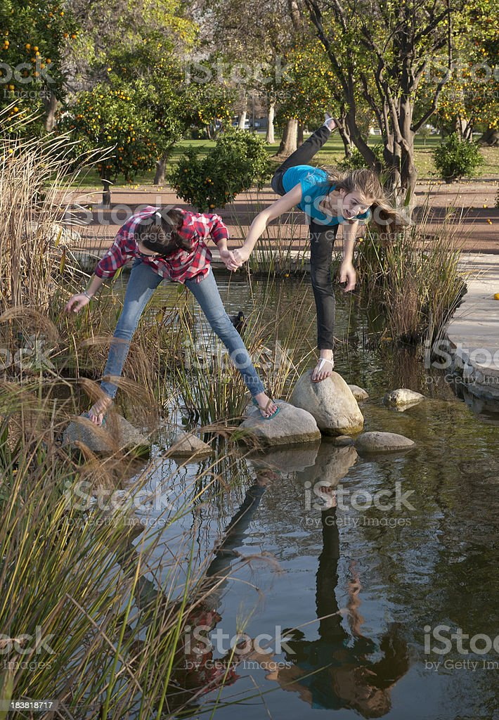 Teen Girls About to Fall Into Stream with Reflection royalty-free stock photo