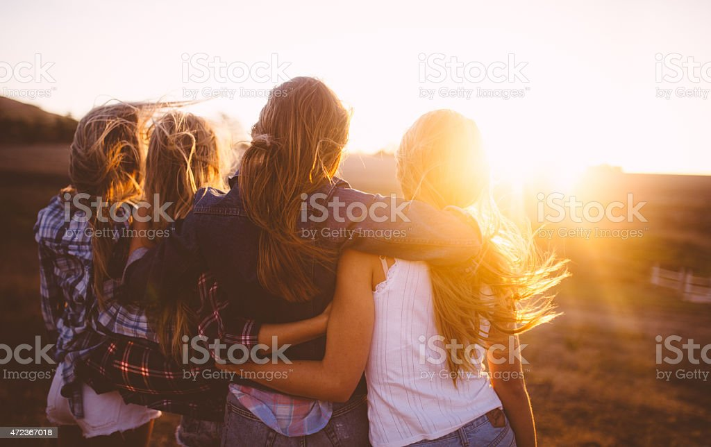 Teen girls facing the sunset with on a summer evening stock photo