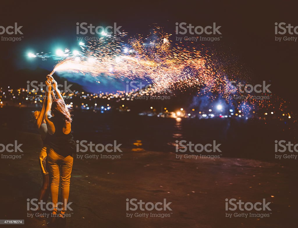 Teen girls holding sparkling fireworks at night at the harbour stock photo